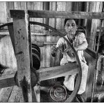 Burma, Inle Lake, Lotus silk: a woman sits before a wooden spinning wheel and ties off a thread