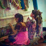 Young women weave silk carpets in Bokhara