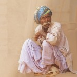 Indian man dressed in pajamas and turban sits in a golden haze