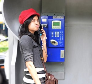 Woman talking on pay phone