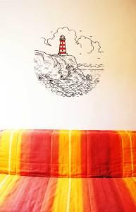 Así de chulo queda nuestro diseño en vinilo del faro decorando la pared de un dormitorio.