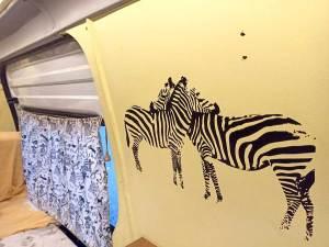 Foto del interior de una furgoneta camperizada decorada con nuestro vinilo de las cebras.