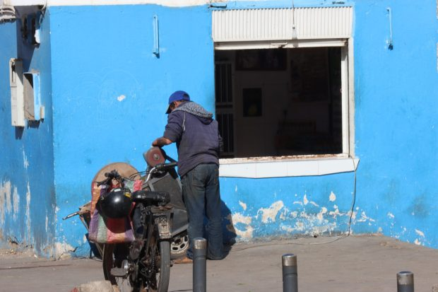 A blue house, man and motor bike