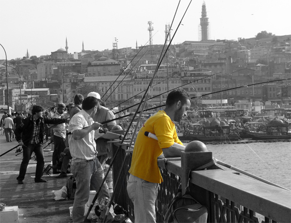 Galata Bridge Istanbul Turkey Fisherman in Yellow Tee shirt