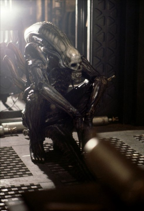 Bolaji Badejo squatting in the Alien suit