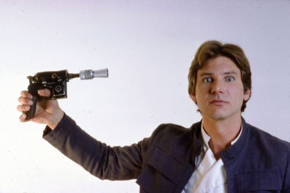 Han Solo (Harrison Ford) pointing a blaster at his head - Star Wars Empire Strikes Back Behind the Scenes