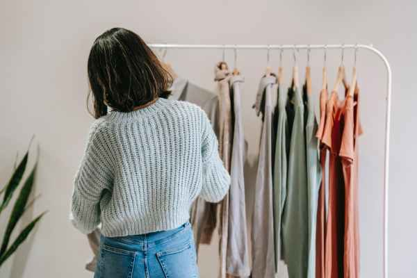 unrecognizable woman against rack with assorted clothes in building