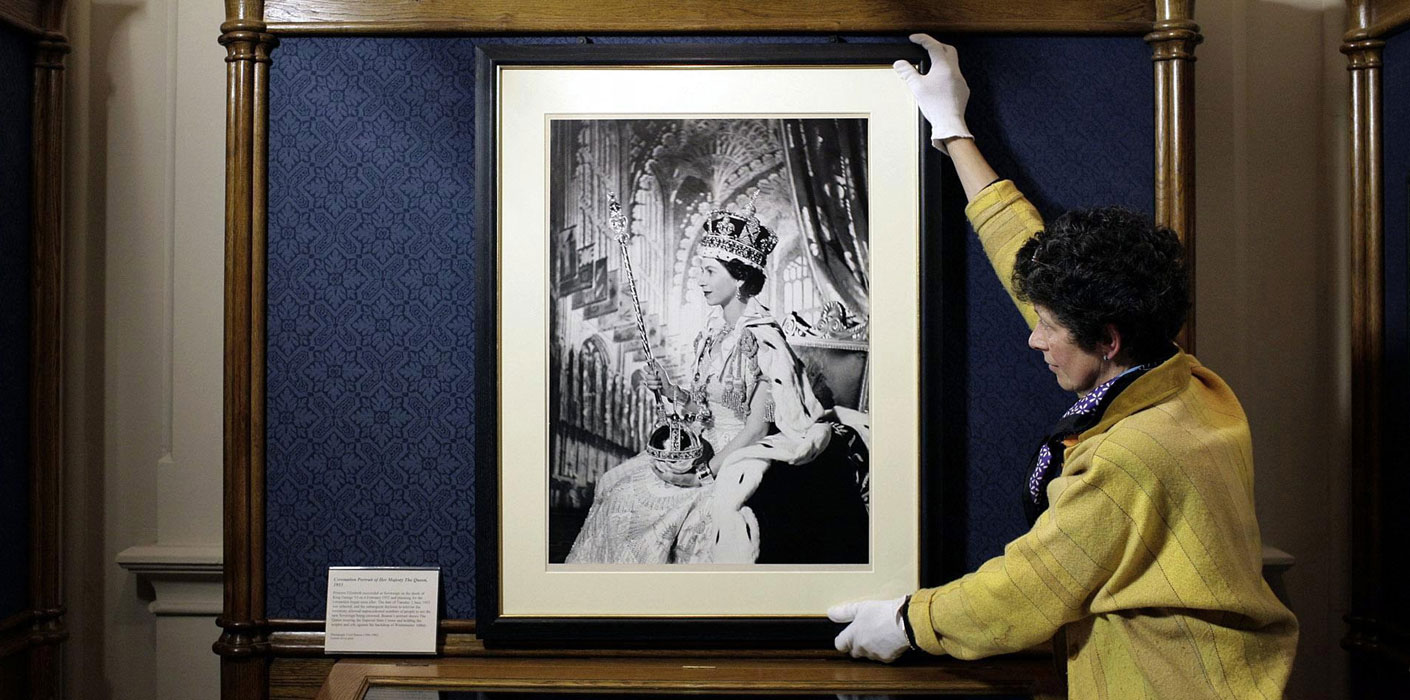 Britian's Queen Eizabeth II by Cecil Beaton from 1953, is prepared by Exhibition Co-ordinator Theresa-Mary Morton