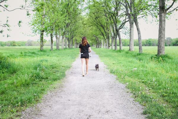 woman and dog walking down path