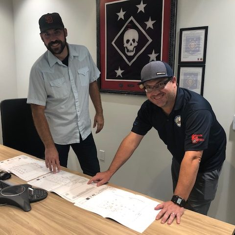 Two employees reviewing drawings.
