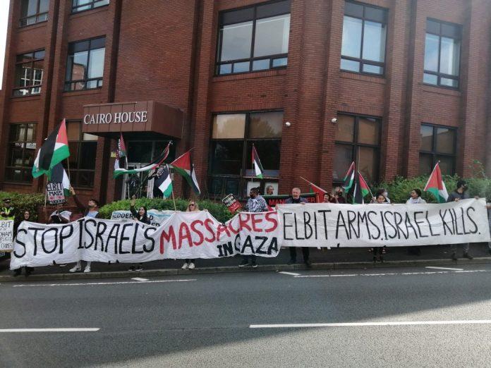 Протестующие вне Каира держат плакаты на обочине дороги.  Баннеры гласят: «Остановить резню Израиля в Газе»;
