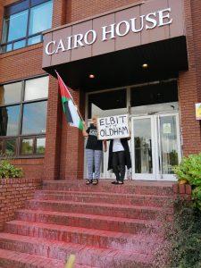 Протестующие сидели за дверным проемом Каирского дома, залитого красной краской.  Табличка гласит: «Эльбит из Олдхэма».