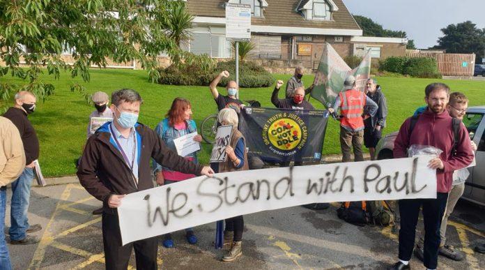 Протестующие в поддержку Пола Холмса.  Баннер гласит: «Мы стоим с Полом».