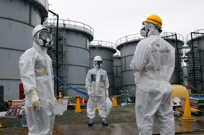 Tokyo Electric Power Corp's (TEPCO) official (C) and journalists wearing protective suits and masks stand in front of storage tanks for radioactive water in the H4 area, where radioactive water leaked from a storage tank in August, at the tsunami-crippled TEPCO Fukushima Daiichi nuclear power plant in Fukushima prefecture November 7, 2013.(Reuters / Kimimasa Mayama)