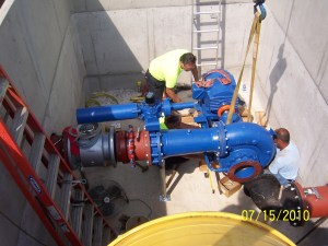 "Workers install Rentricity's turbine and generator at a pump station for the Municipal Authority of Westmoreland County near Pittsburgh. The ""behind-the-meter"" 21-kW installation powers two of four large horsepower pumps that send water up hill to a treatment plant 2,500 feet away. (Source: Rentricity Inc.)"