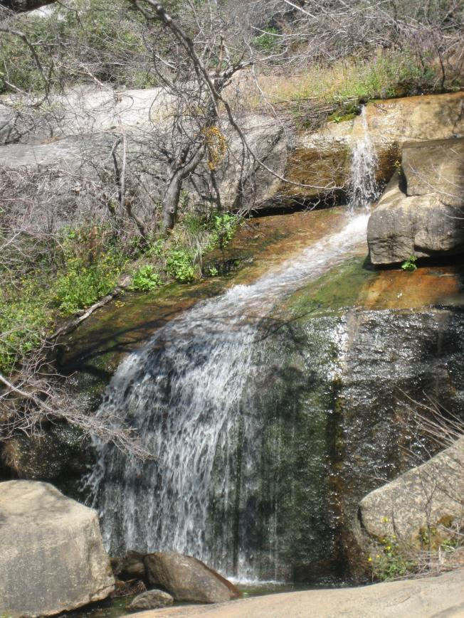 Unnamed waterfall next to a gravel road.