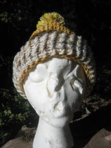 This hat, modeled by Esmerelda, has an autumn color scheme of browns, golden yellows, and oranges. In this view, the finished edge brim is folded back. The pompom on top is super cute, and the cost is $13, including postage.