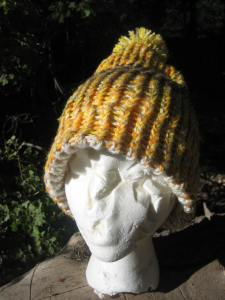 In this view of the same hat with an autumn color scheme and a pompom. the finished edge is folded down for extra ear coverage. Any hat with a finished edge can be worn with the brim folded up or down. Again, the cost of this hat is $13, including postage.