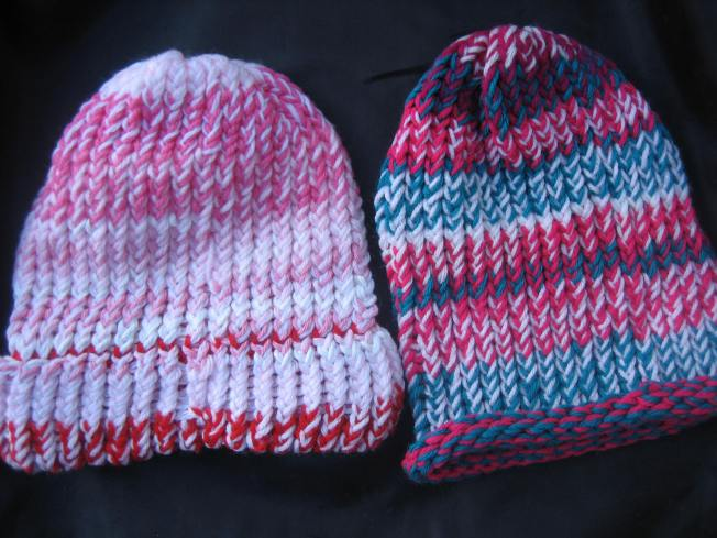 These two large hats both sport a pink color scheme, although the one on the left is softer pink with red and white, and the one on the right is hot pink and bright blue. The soft pink hot has a finished edge that can be folded up or worn down for added ear coverage. The hot pink hat has a rolled edge. Both hats cost $13, including postage.