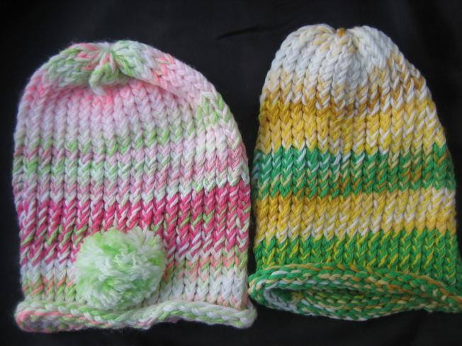 These large hats both boast green. The hat on the right has a pink and green color scheme and a whimsical pompom front and center. The hat on the left includes green and white and variety of yellows. Both hats have a rolled edge, and both cost $13, including tax.