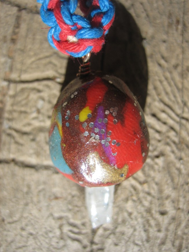 This mushroom has a lot of color. The cap is made from clay and includes browns, reds, yellows, blues, and GLITTER. The stem is a QUARTZ CRYSTAL. I used blue and red hemp to make the necklace, matching the blue and red of the mushroom cap. The necklace can be worn with either the mostly blue side or the mostly red side showing, so it's like getting two necklaces in one. The necklace is 20 inches long. The price is $23, including postage.