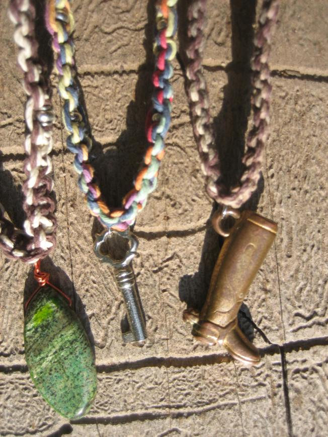 The necklace on the left is made with brown and natural hemp and has a serpentine pendant. Serpentine is believed to help the wearer feel more in control of his or her life. It aids meditation and spiritual life. This necklace is 20 and 1/2 inches and costs $16, including postage. The middle necklace has an ornate little key on rainbow hemp. It is 18 and 1/2 inches and cost $12, including postage. The necklace on the right boasts a metal boot on earth tone hemp. It is 19 and 1/2 inches and cost $10, including postage.
