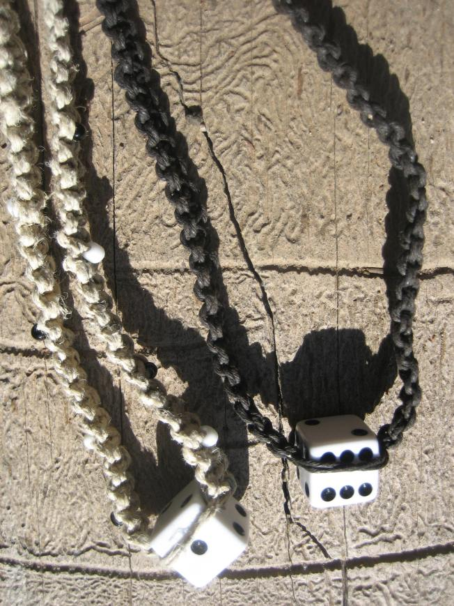 These two necklaces feature dice I drilled. The necklaces made from black hemp is 15 inches long. The necklace made from natural hemp is 20 inches long and has black and white accent beads.
