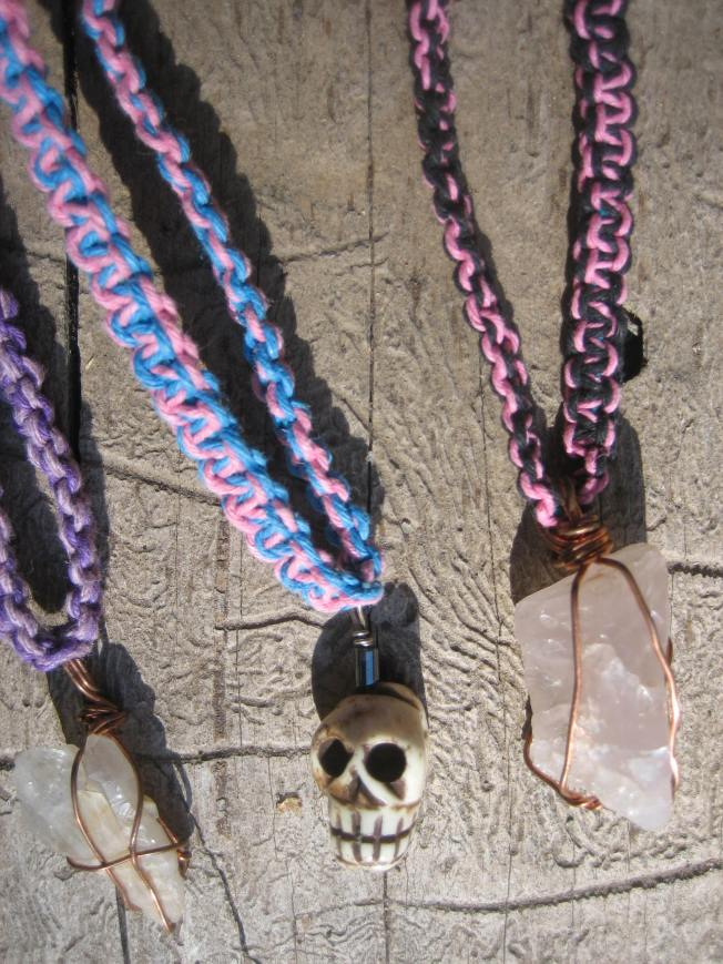 I made the pendant on the necklace on the left. The hemp is purple and black. The stone is a double quartz crystal. Quartz is believed to be a powerful healer and energy amplifier that unlocks memory. This necklace is 21 inches long and costs $18, including shipping. The middle necklaces features a skull pendant carved from smoked yak bone with hematite accent beads. Hematite is believed to dissolve negativity and enhance willpower. The pink and blue hemp portion is 17 inches long. The cost, including shipping is $18. The necklace on the right features a pendant I made. The stone is rose quartz from South Dakota. Rose quartz is the stone of unconditional love and infinite peace. It is believed to encourage self-forgiveness. This necklace is 20 inches long and features pink and black hemp. The cost is $15, including shipping.