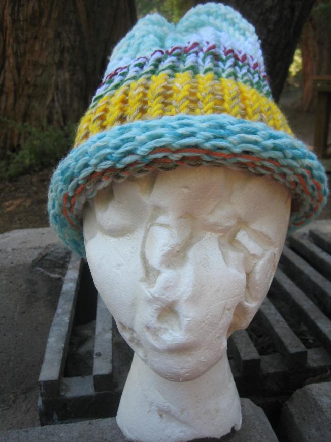 This large hat features a variety of colors: blue, orange, yellow, purple. It has an unfinished edge and costs $13, including shipping charge.