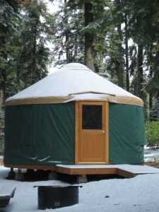 A green yurt with a brown door is covered with a dusting of snow. Snow is on the ground in the foreground and trees are in the background.
