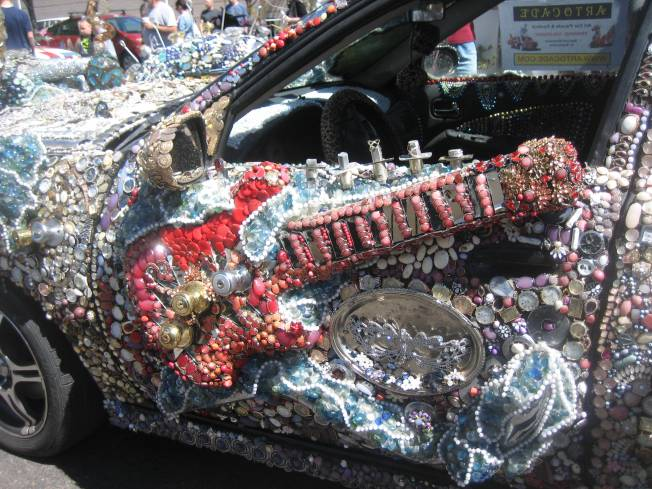 A red guitar is attached to the driver's door of a meticulously embellished art car.