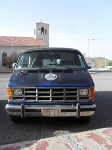 An old blue Dodge van is parked. In the background is a Catholic church.