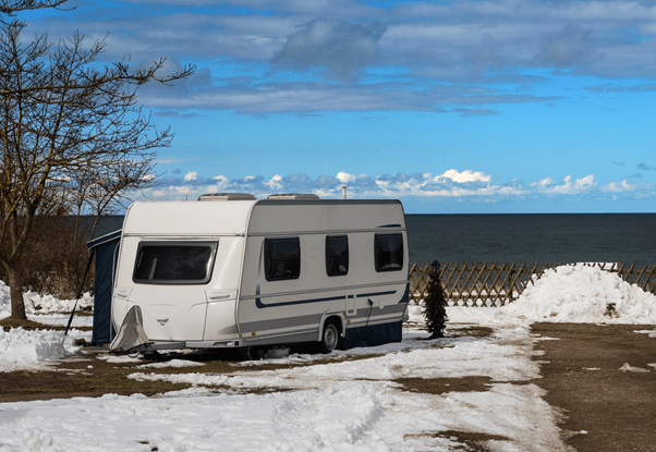 A travel trailer sits in the snow near a leafless tree. A lake is in the background. The sky is blue with grey clouds up high and puffy white clouds down low.