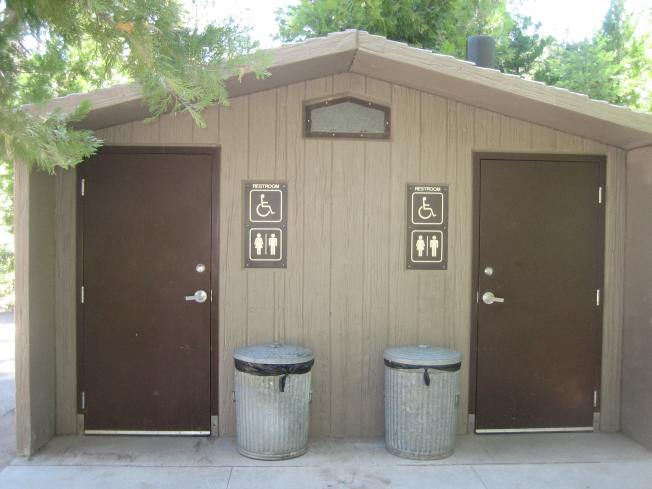 Small building with two doors, each with a restroom sign next to it. Two metal trash cans sit outside the building.