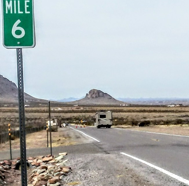 Green mile marker sign with a 6 on it is in the foreground. A motorhome is driving away from the camera, towards the mountains.