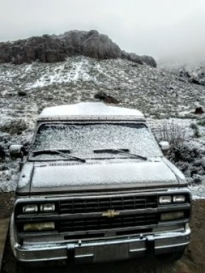 Chevy G20 van dusted with snow sits in front of a small, rocky mountain.
