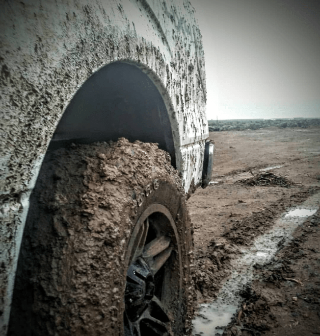 Tire and fender covered in mud. Large rut filled with water in the background.