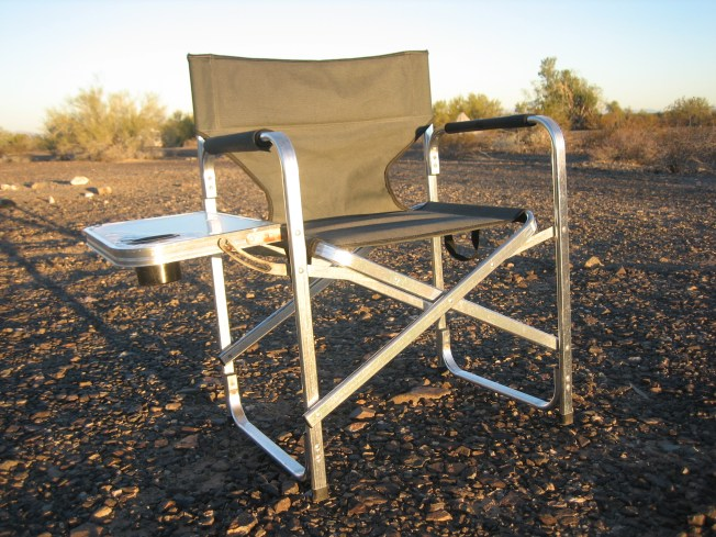 Green camping chair sitting alone in the sunlight.