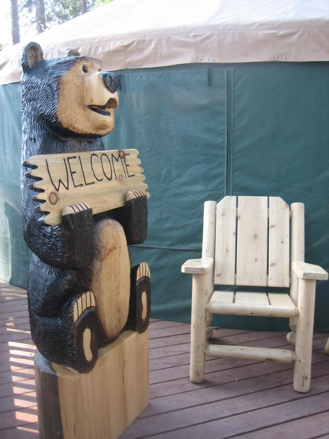 "A large bear carved from wood sits next to a wooden chair and holds a sign that says ""welcome."""