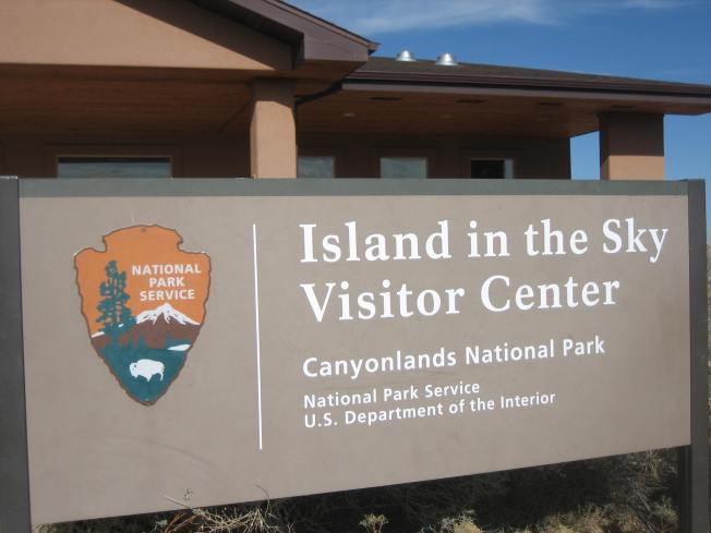 Sign with National Park Service logo on it and the words Island in the Sky Visitor Center Canyonlands National Park National Park Service U.S. Department of the Interior