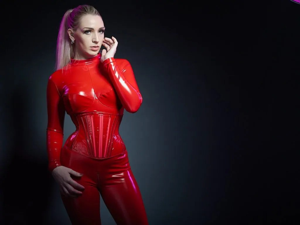 Blonde and gorgeous real time BDSM seattle prodomme Ruby Enraylls in patent black gloves