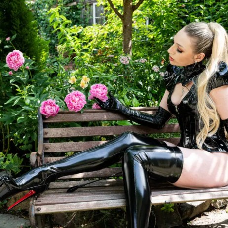 Seattle dominatrix Ruby Enraylls sits in the garden of hedon wearing a latex outfit, contemplating dominating you and making your bdsm dreams become a kinky reality.