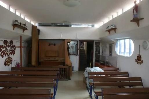 L'intérieur de la chapelle, dans l'ancienne partie transport de la péniche. Au fond à gauche, un orgue pour l'office. Au mur, un chemin de croix illustré en bois ouvragé. Au fond à droite, la maquette d'un ancien bateau remorqueur dans sa vitrine. ©MP/Rue89Lyon