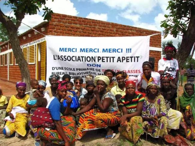 """Des habitants au Burkina Faso devant une école construite grâce aux dons récoltés par l'association """"Petit à Petit"""". (document transmis)"""