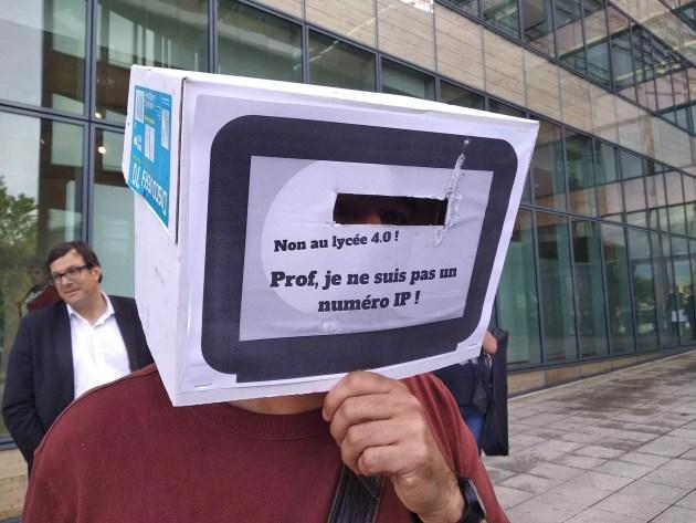 """Un participant a posé un carton en forme de télévision sur la tête. """"Prof, je ne suis pas un numéro IP""""."""
