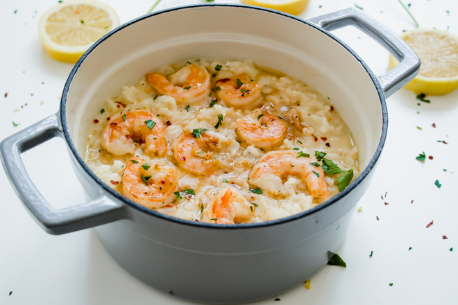 gray pot of risotto with shrimp scampi on top