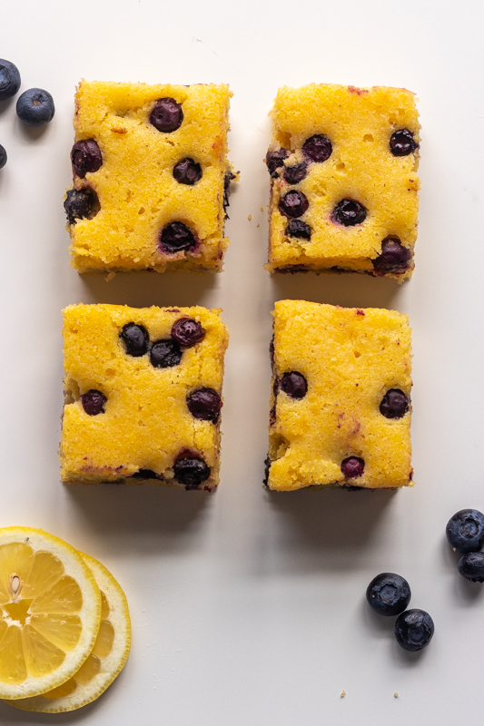 close up flatlay of four pieces of blueberry cornbread with lemons and blueberries surrounding it