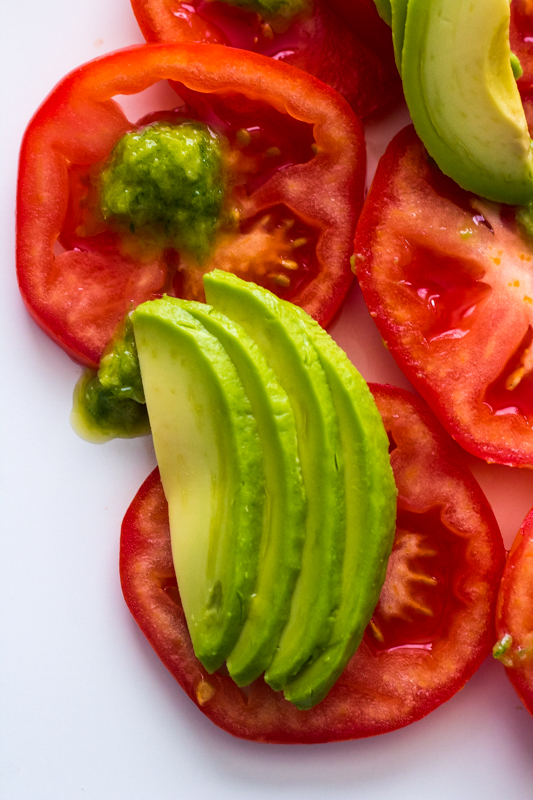 close up of avocado tomato salad on a white plate