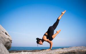 woman doing yoga pose on rocks