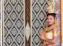 Thai Maedchen in traditionellem Kostuem macht das Wai